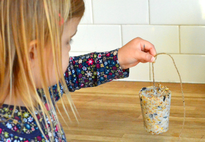DIY bird feeder being held up by a little girl