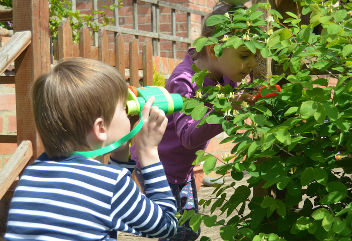 Little boy with binoculars looking into a bush